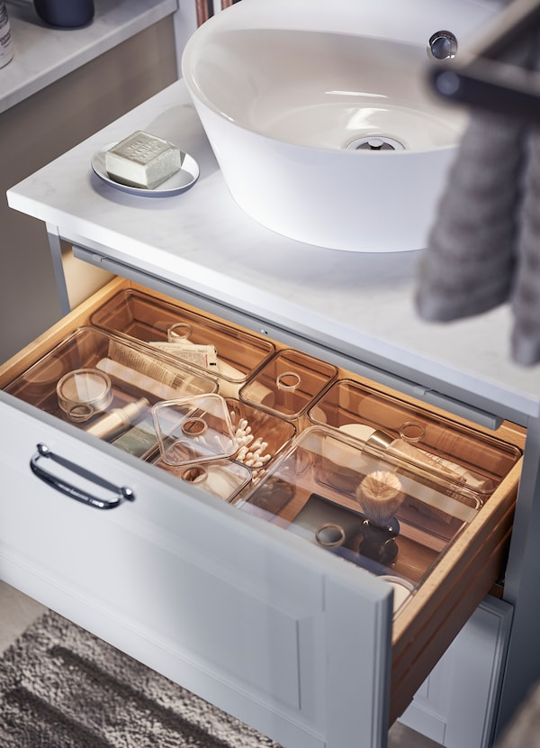 Organise your bathroom drawers with transparent GODMORGON organiser boxes. The clear plastic lids have a small whole in the center for ventiliation and so you can open the box with just a finger.