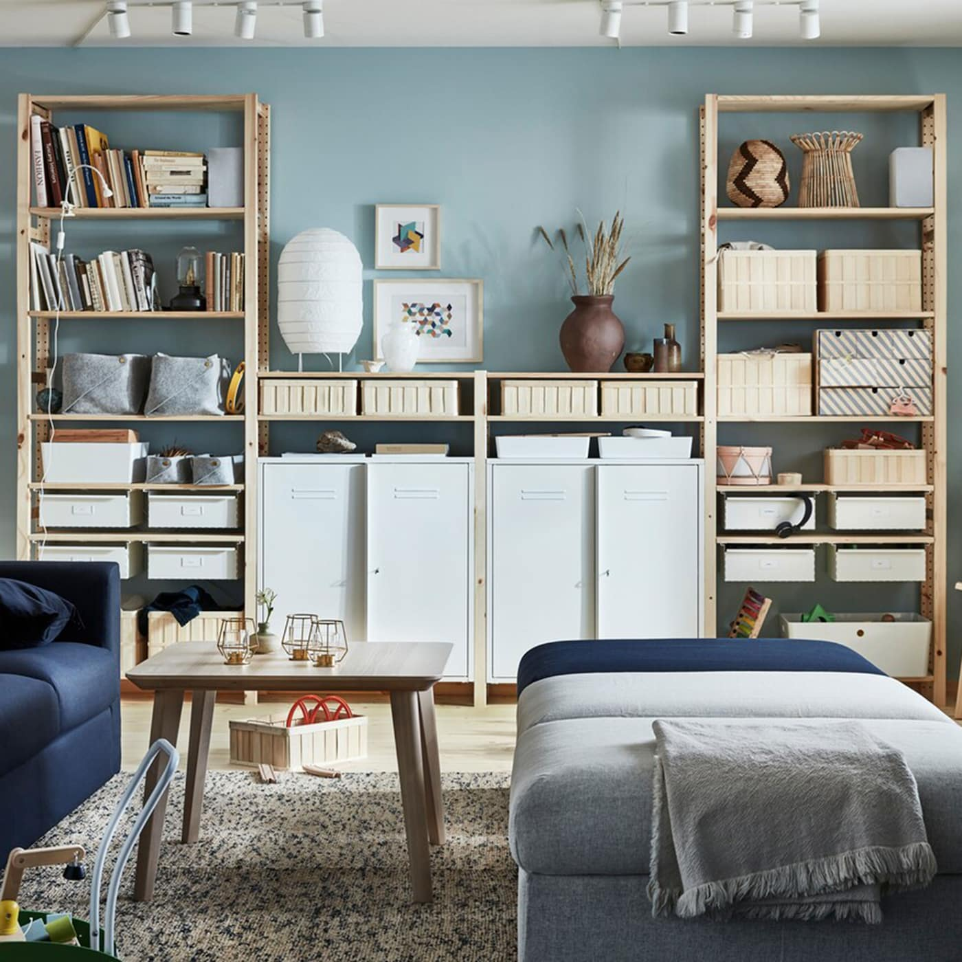 Organise your living room with IKEA IVAR furniture storage system. The light pine wood shelves are customisable to fit many different box heights.