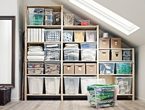 Organised storage under slanted ceiling with IVAR shelving unit and SAMLA storage boxes.