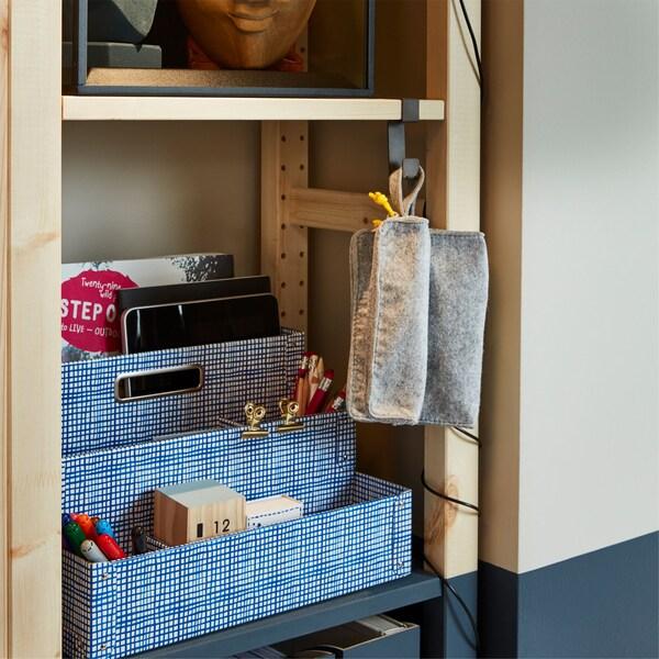 Organizador de escritorio IKEA FJÄLLA en blanco y azul en baldas IVAR y un gancho gris IKEA IVAR utilizado para colgar otros artículos.