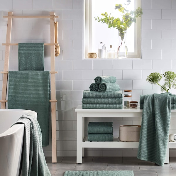 Organized bathroom shelves with towels and other bathroom essentials.