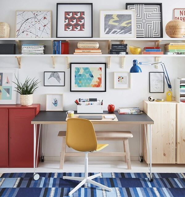Organized desk in a cool workspace with art on the walls and shelves, a blue lamp and a plant