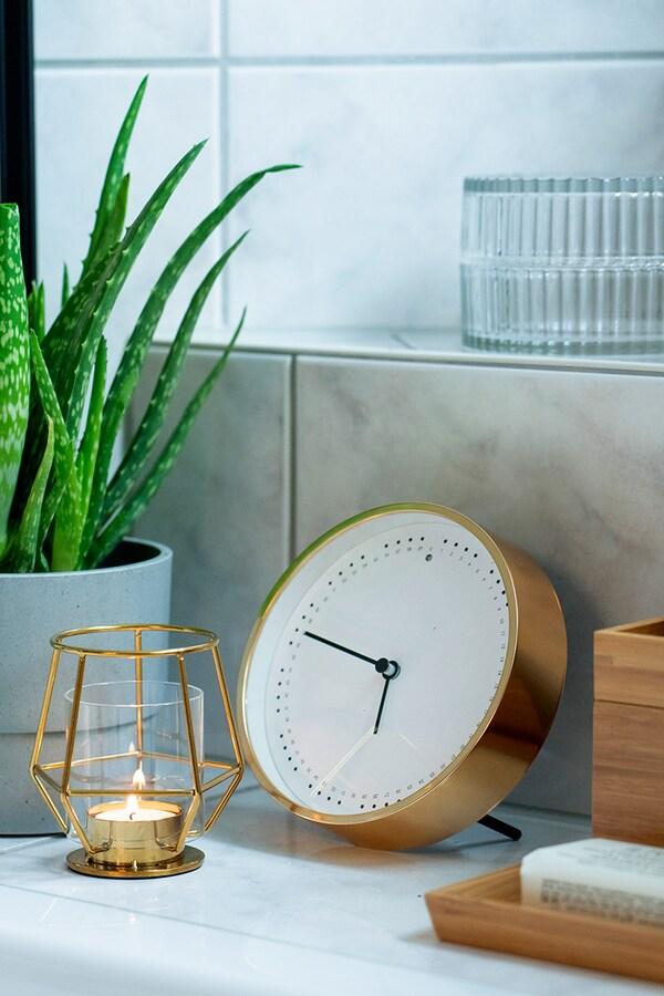 Orologio IKEA in combinazione con la candela IKEA e la pianta nel bagno.