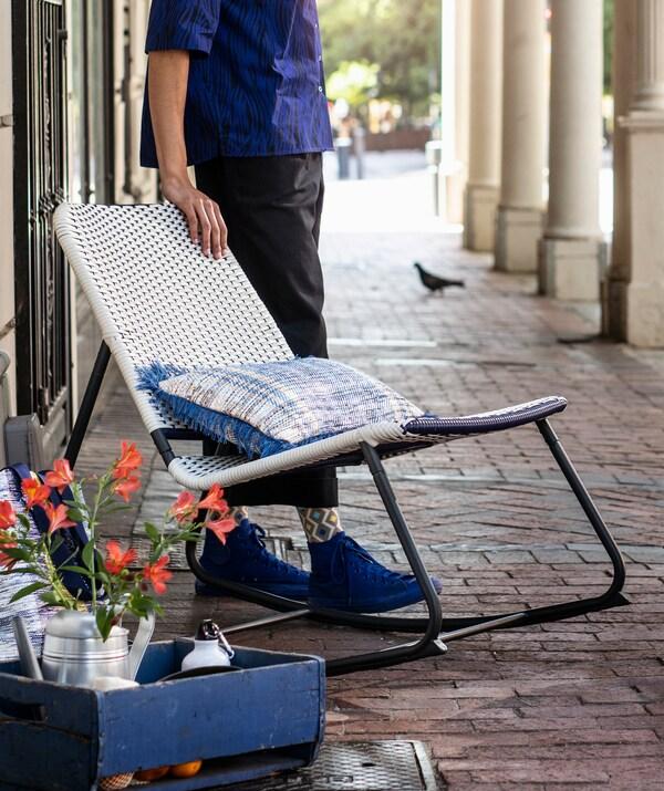 Osoba stojąca na świeżym powietrzu obok niebiesko-białego krzesła bujanego z metalową ramą.