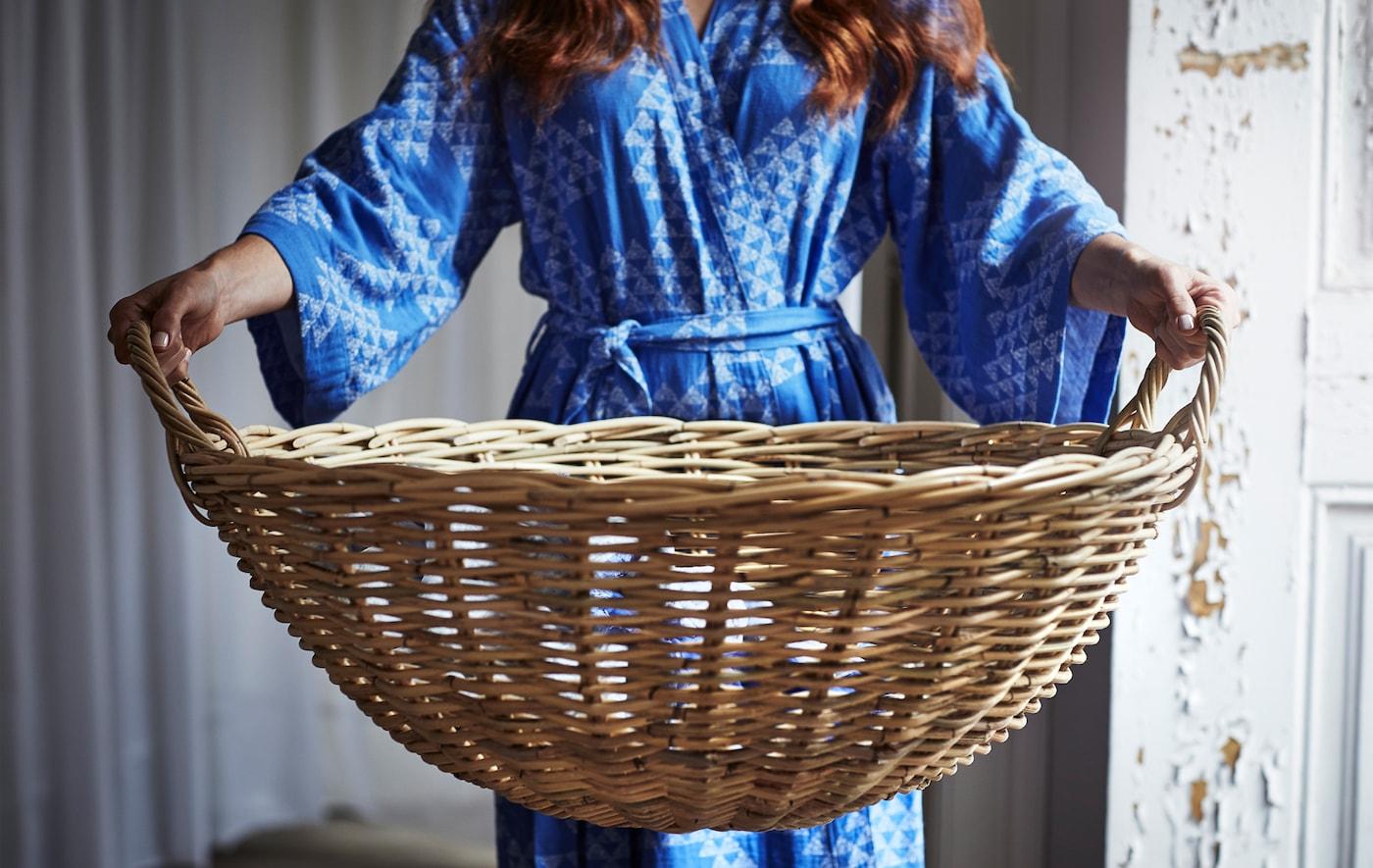 Osoba w niebieskim, wzorzystym kimono trzyma duży, okrągły rattanowy kosz.