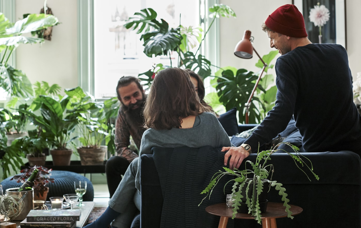 Ospiti seduti su un divano in velluto blu scuro in un soggiorno decorato con piante e tessili a stampa botanica - IKEA