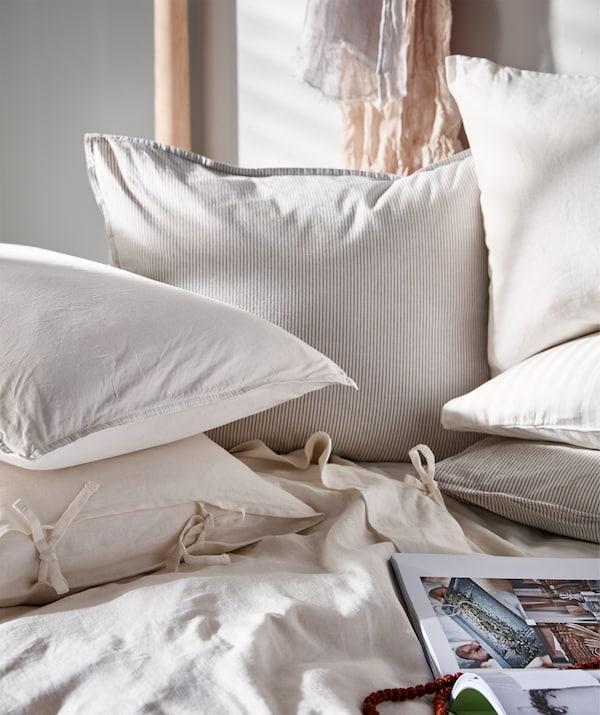 Osunčan krevet s puno jastuka i jastučića od tekstila svetlih nijansi, otvorena knjiga na jorganu.
