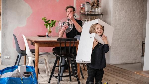 Otec s dcérou v jedálni, otec sedí za stolom a dcéra sa hrá s kartónovou škatuľou.