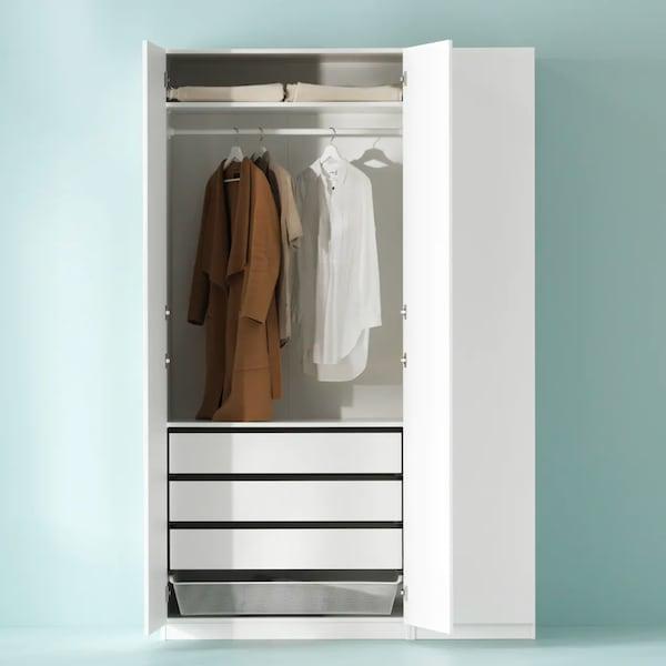 Otevřená bílá šatní skříň s ramínky a šuplíky uvnitř.