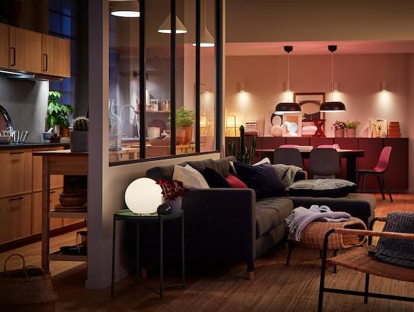 Otevřený obývací pokoj s jídelnou a kuchyní, v něm řada různého chytrého osvětlení TRÅDFRI.