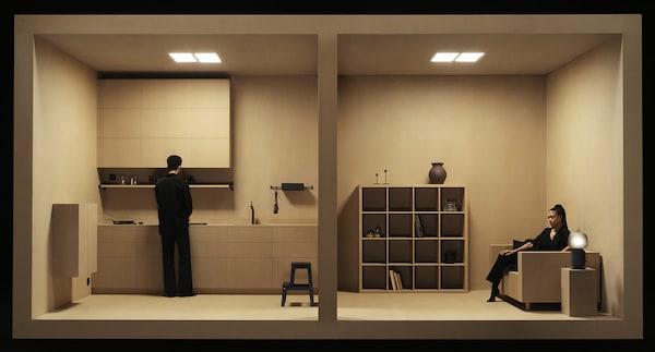 Otevřený prostor vytvořený z papírové lepenky, u kuchyně stojí muž, v obývacím pokoji sedí na pohovce žena. Vedle pohovky na stolku stojí lampa SYMFONISK.