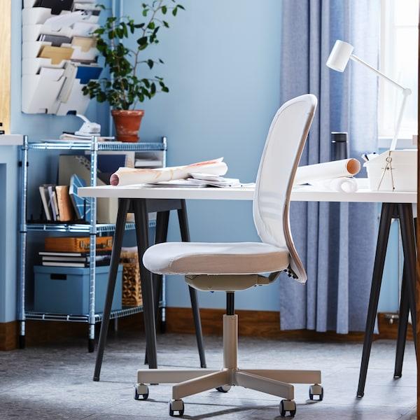 Otočná židle FLINTAN vedle bílého stolu apolicového dílu OMAR naplněného papíry akrabicemi vmodré kanceláři.
