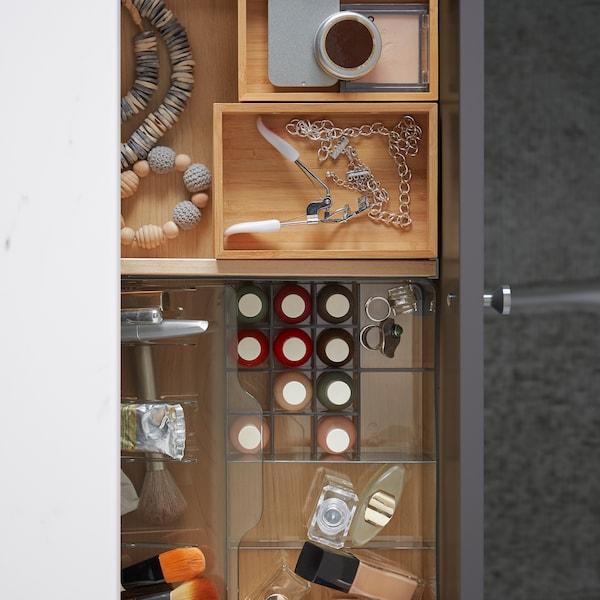 Otvorena kupatilska fioka s elementom od providne plastike za šminku, i DRAGAN kutijama od bambusa s dodacima.
