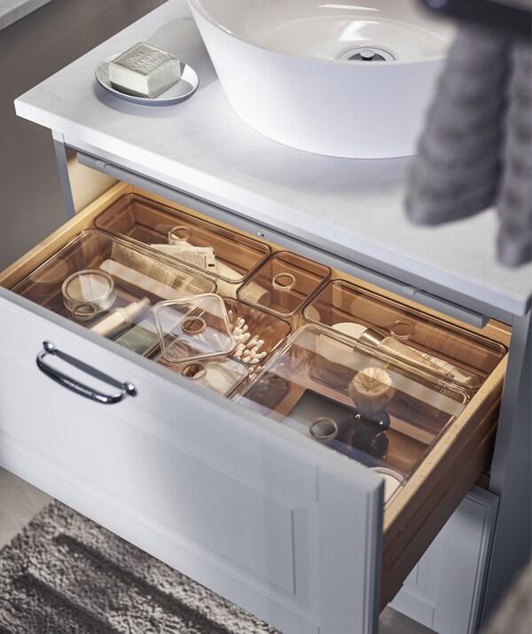 Otvorena ladica sivog elementa s umivaonikom. U njoj se nalaze uredno organizirane kupaonske potrepštine u prozirnim plastičnim umetcima.