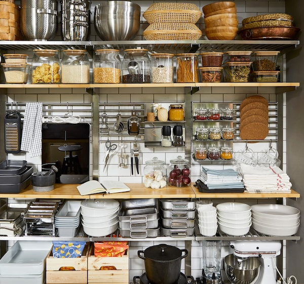 Otvorene kuhinjske police od drveta, uz kuhinjski alat poput TILLREDA prenosive indukcijske ploče i KUNGSFORS stalka za tablete, sa začinima.