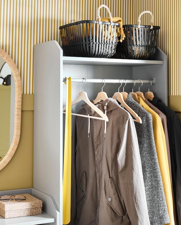 Otvoreni garderober sa šipkom o koju su zakačene jakne pomoću vešalica od punog drveta, kao i gornja polica s dodacima raspoređenim u dve crne korpe.