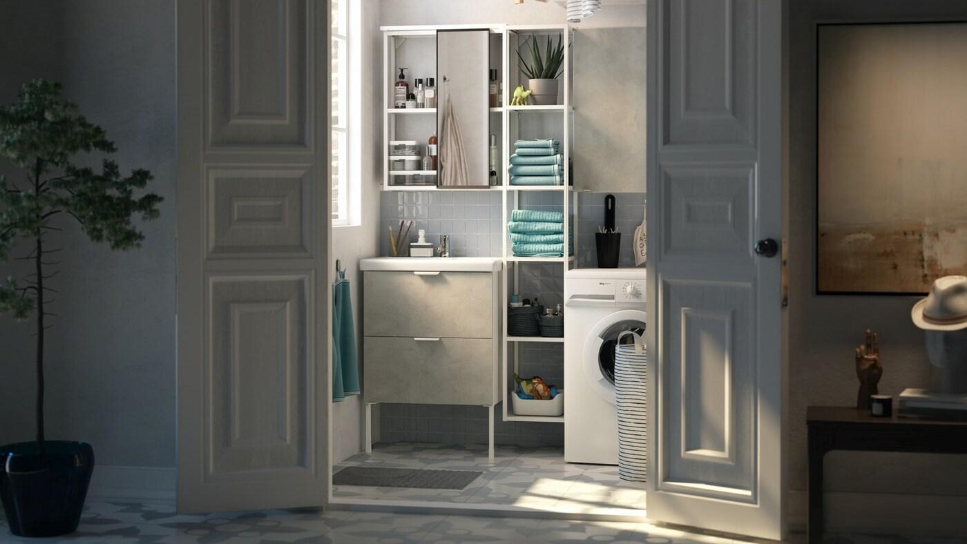 Otwarte białe drzwi prowadzące do niewielkiej łazienki z wąskim białym regałem ustawionym między białą umywalką i pralką.