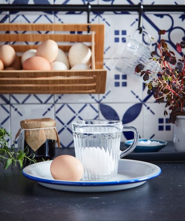 Ouă pe o farfurie, cu un ou pe fundul unei căni DRÖMBILD pline cu apă. Coș cu ouă agățat pe fundal.