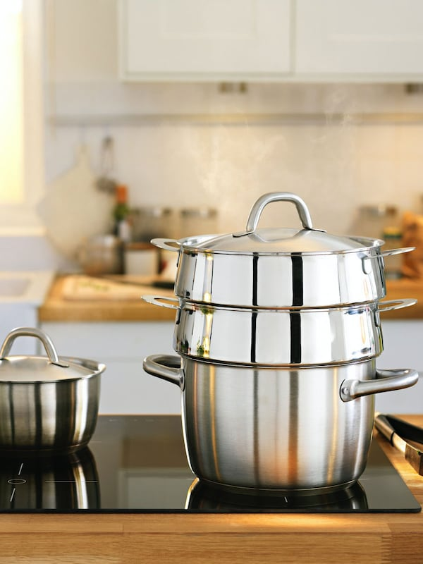 OUMBÄRLIG cookware set on an induction hob in a white modern kitchen with wooden counter top