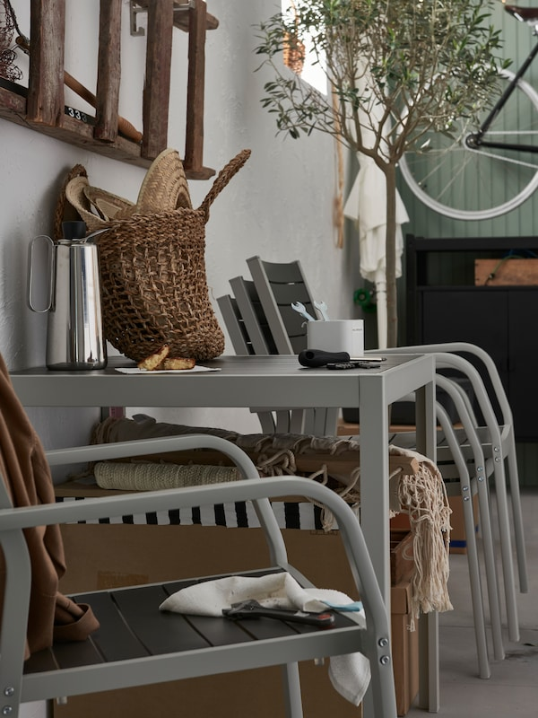 Outdoor chairs, one individual chair and others stacked next to a wall, along with an outdoor table with a coffee pot, purse and tools.