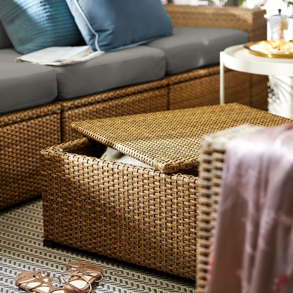 Outdoor footstool with storage space in faux rattan.