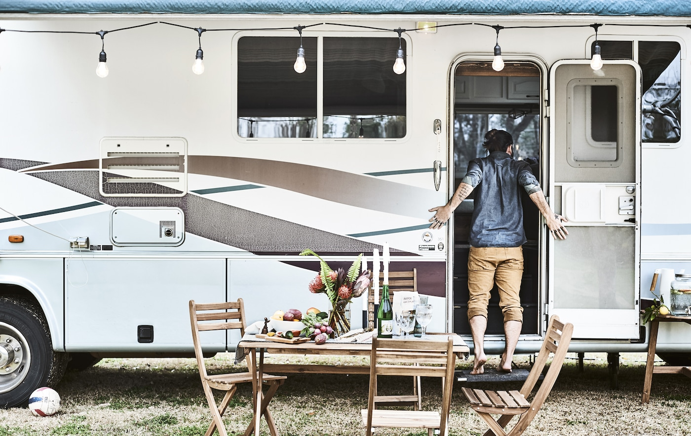 Outdoor furniture outside a motorhome decorated with lights, where Karlton stands in the doorway.
