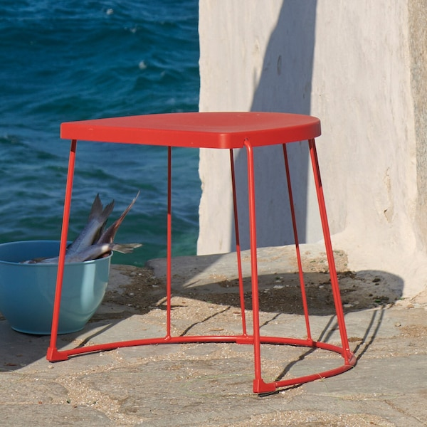 Outdoor scene, with a red stool.
