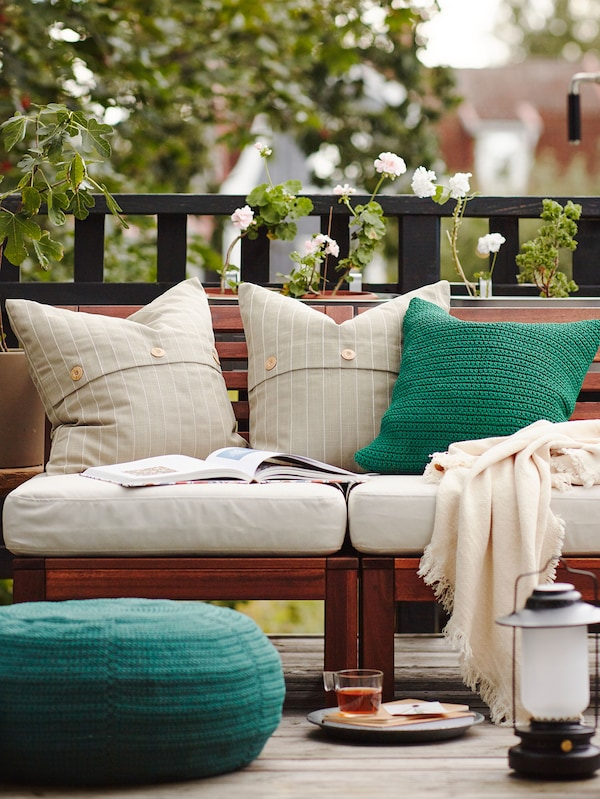 Outdoor seating with beige and green cushions, and a green pouffe.