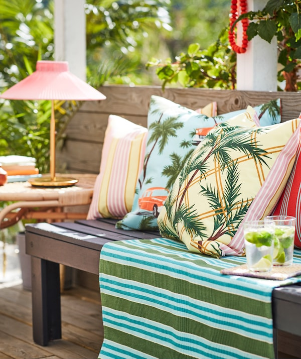 Outdoor setting with a wooden bench semi-filled with cushions with SOMMAR 2020 covers. A SOLVINDEN lamp stands nearby.