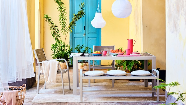 Outdoor space with a big table prepared for a meal outside, 2 chairs and a bench.