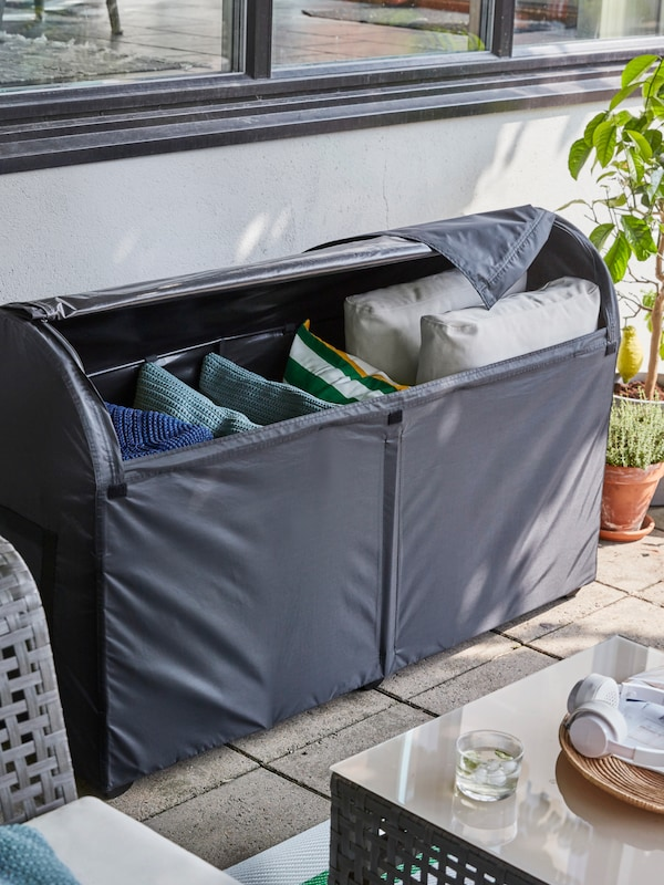 Outdoor storage in dark gray, containing larger and smaller cushions, on a terrace beside some potted plants.