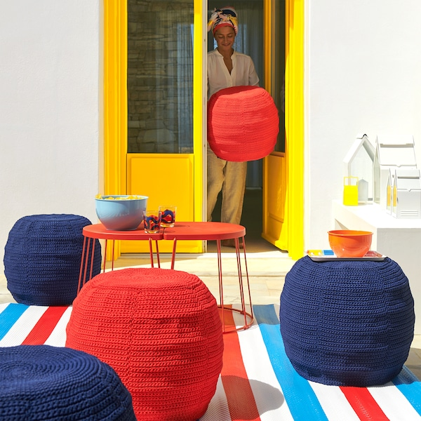 Outdoor summer scene, with table and OTTERÖN/INNERSKÄR pouffes with crocheted covers.