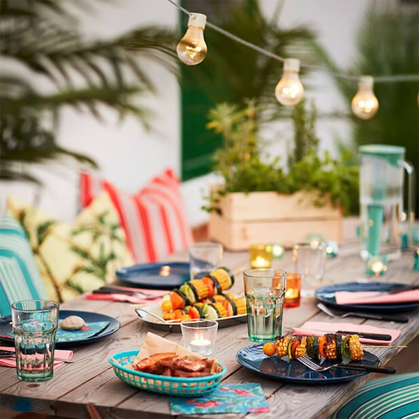 Outdoor table with colourful dishes, with string lights hanging overhead.