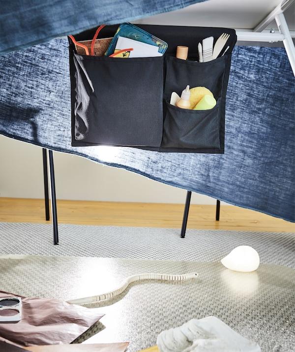 Outils de jeune artiste dans un rangement à poches suspendu sous une table de salle à manger; un tissu tombant sur les côtés forme un mini-studio temporaire.