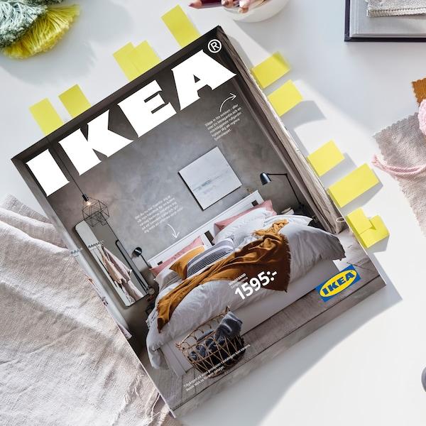 Ovanifrån syns den nya IKEA katalogen med diverse pyssel och tygbitar bredvid på en grå bakgrund
