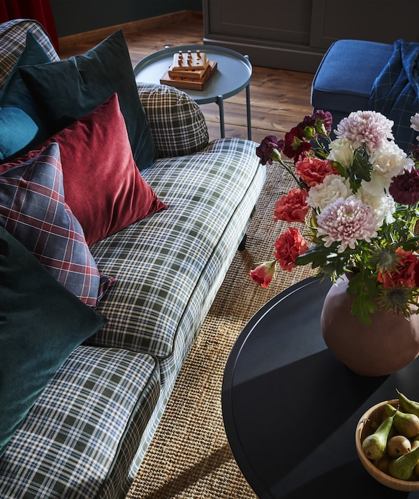 Overhead view of a tartan sofa and coloured cushions next to side tables and vase of flowers.