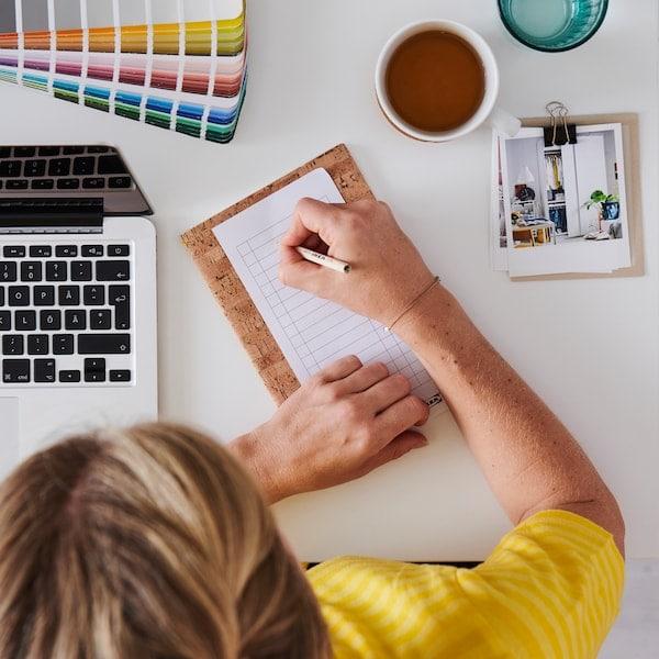På en platt vit yta står pennor, anteckningsblock, tygbitar och en sax.