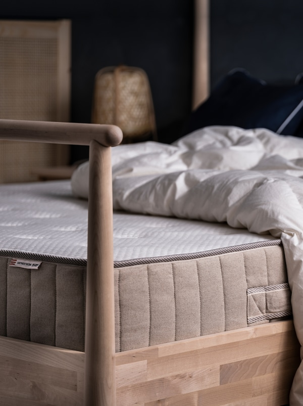 På et GJÖRA sengestel af birk i et soveværelse med en blød belysning ligger en VATNESTRÖM madras og en dyne, begge uden sengetøj.