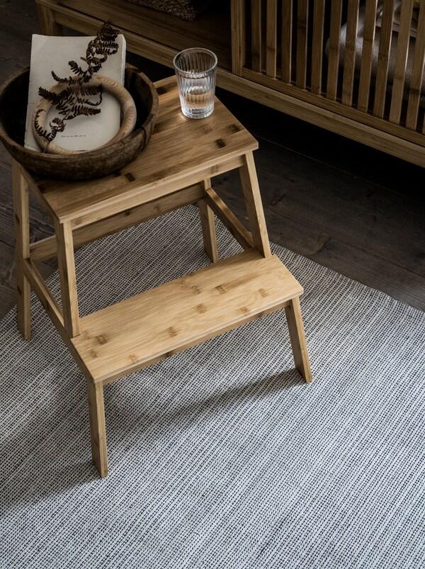 På et TIPHEDE tæppe af genanvendt bomuld står en TENHULT taburet af bambus. På taburetten står et glas vand og en lille kurv.