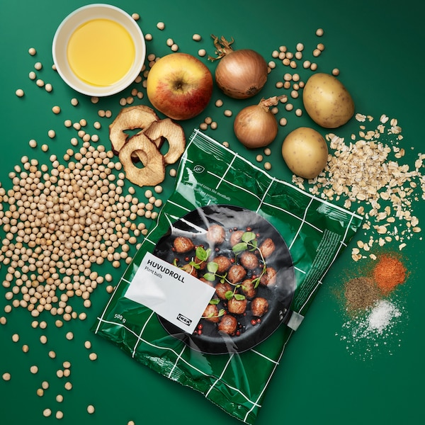 Package of HUVUDROLL plant balls, surrounded by the ingredients: peas, oats, potatoes, onions, apples, spices.