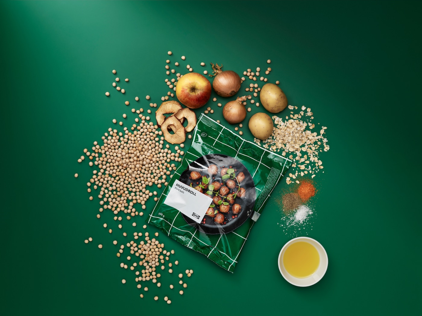 Package of HUVUDROLL plant balls, surrounded by the unprocessed ingredients: peas, oats, potatoes, onions, apples, spices.