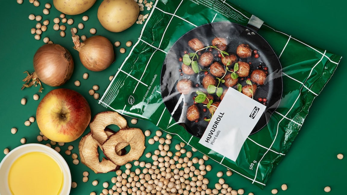 Package of HUVUDROLL plant balls, surrounded by the unprocessed ingredients: peas, oats, potatoes, onions, apples and spices.