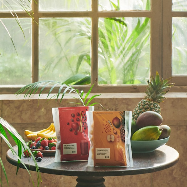 Packages of FRUKSTUND pre-blended smoothie mixes with a yellow tropical mix and a red strawberry blend, placed on a table.