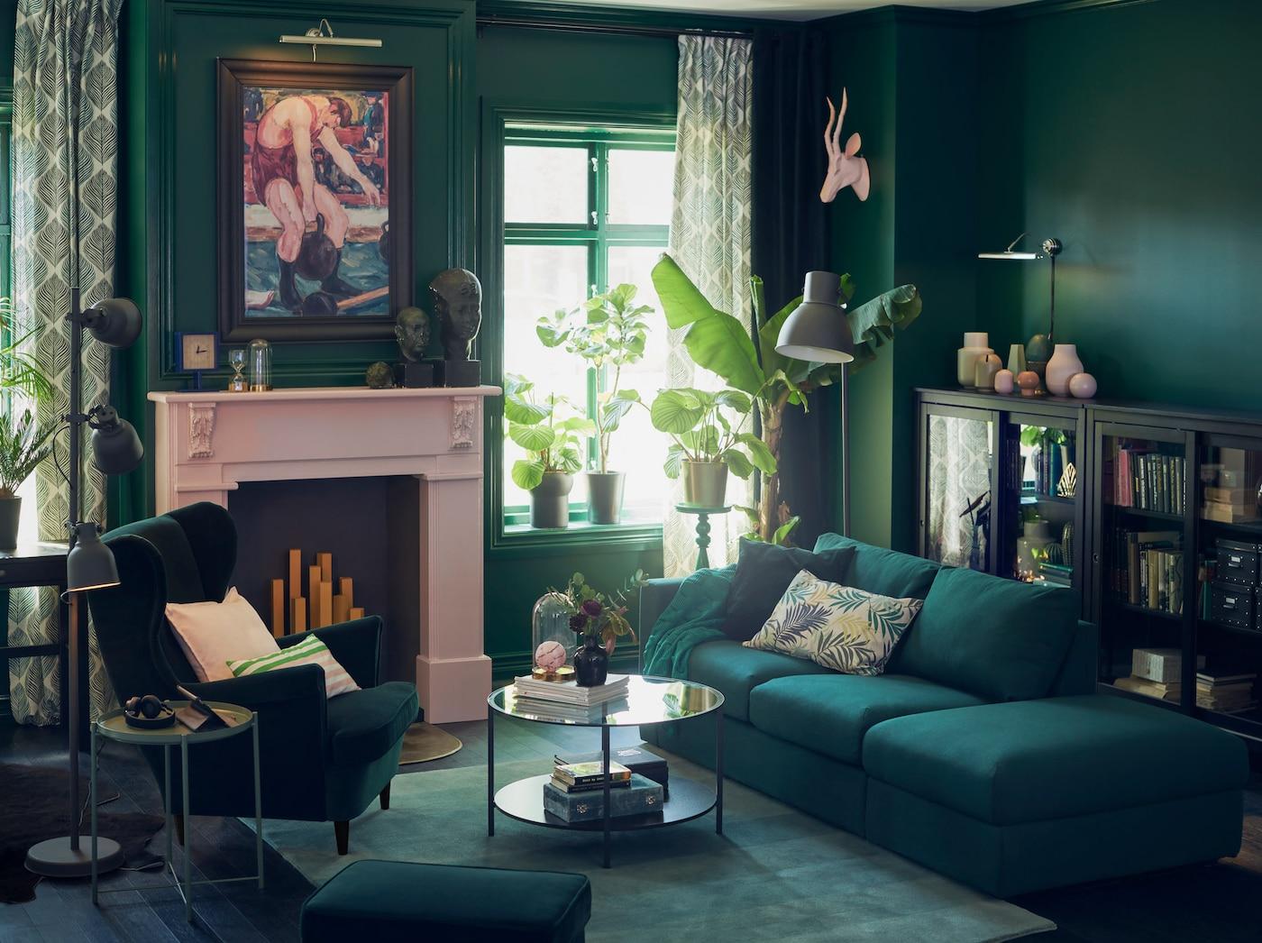 Päästä avoin tummanvihreä sohva lepotuolia vastapäätä vihreässä olohuoneessa, jossa roosanvärinen takka.