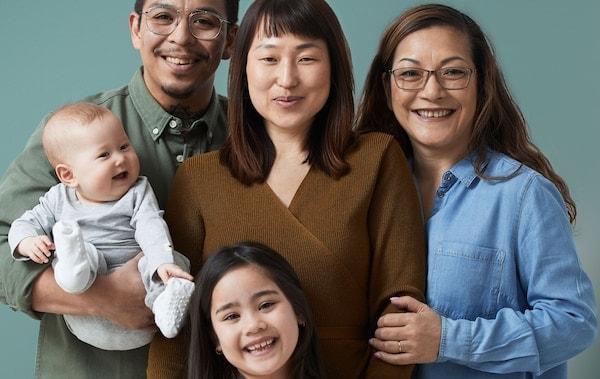 Päťčlenná usmiata viacgeneračná rodina s bábätkom, dcérou a starou mamou.