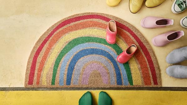 Paillasson arc-en-ciel PILLEMARK sur un plancher à côté de chaussures colorées et d'une paire de pieds enchaussettes.