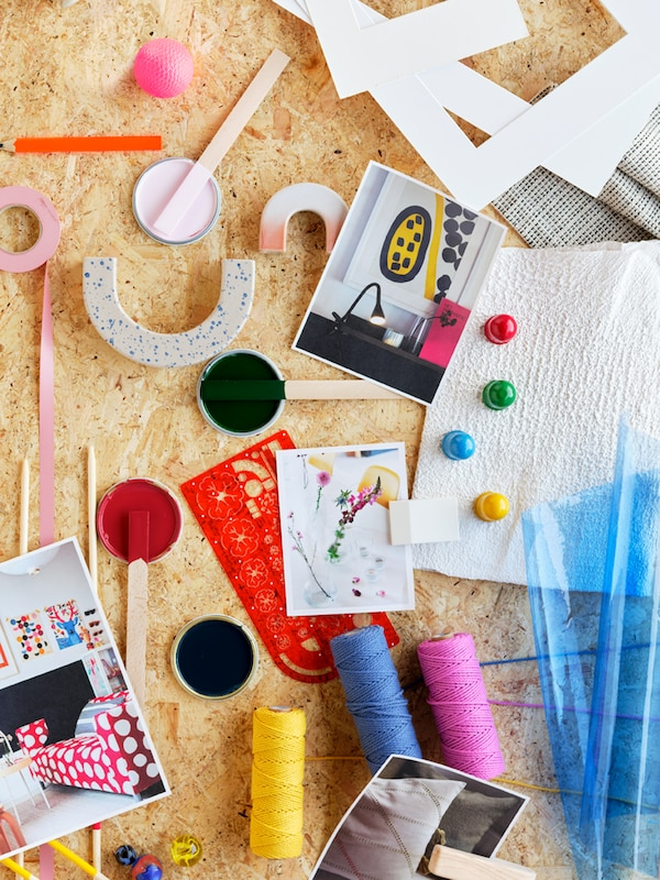 Paint sticks and small containers of colour, coloured threads, passe-partouts and photographs scattered on a wooden surface.