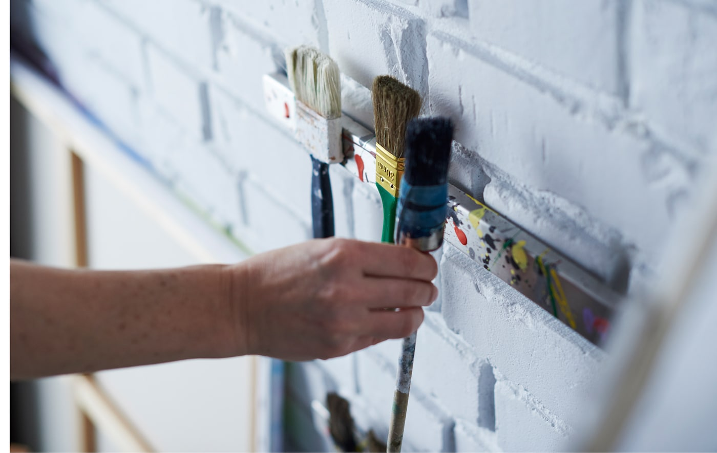 Paintbrushes are being mounted to a magnetic knife rack on the wall.