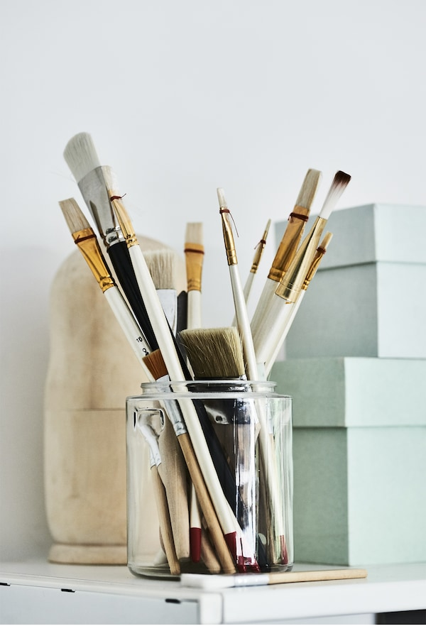 Paintbrushes stored in a glass jar.