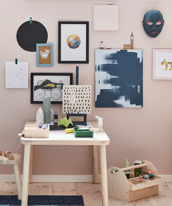 Paintings and drawings displayed on a pink wall above a light wooden desk.